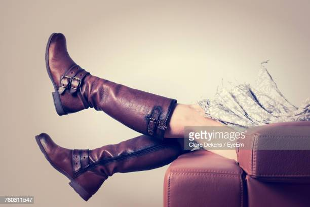 low section of woman wearing boot lying on sofa at home - brown shoe stock photos and pictures