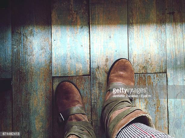 Low Section Of Woman Wearing Boots On Wooden Floor