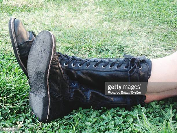 low section of woman wearing boots resting on grass - black boot stock pictures, royalty-free photos & images