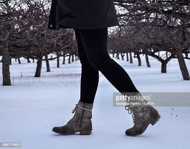low section of woman wearing boots walking on snow covered field - ブーツ ストックフォトと画像