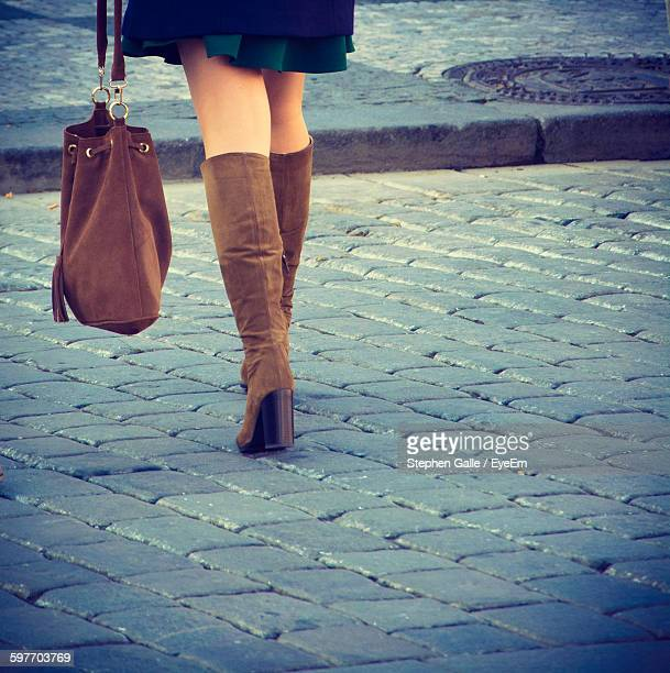 Low Section Of Woman Wearing Boots Walking On Street
