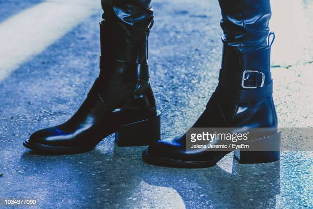 low section of woman wearing boots while standing on road - leather boot stock pictures, royalty-free photos & images