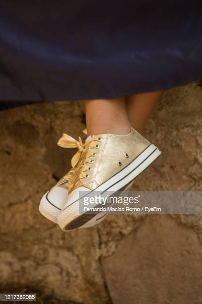 low section of woman wearing canvas shoes outdoors - legs crossed at ankle stock pictures, royalty-free photos & images