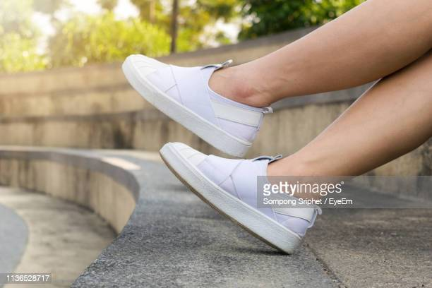 Low Section Of Woman Wearing Canvas Shoes Sitting On Steps