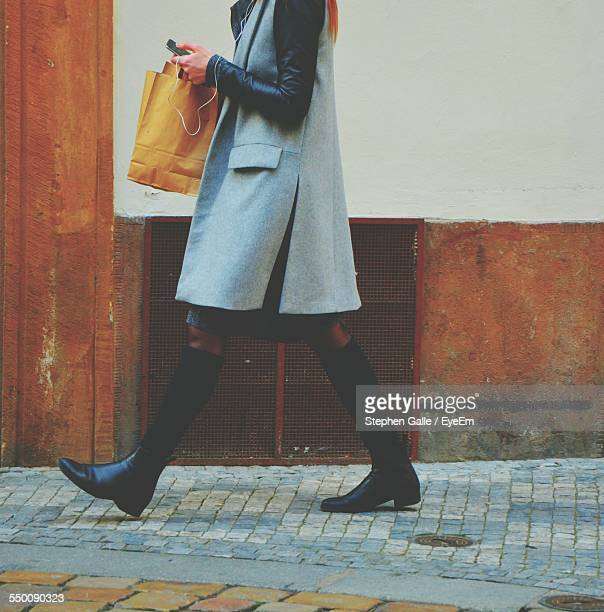 Low Section Of Woman Wearing Coat On Sidewalk Against Wall