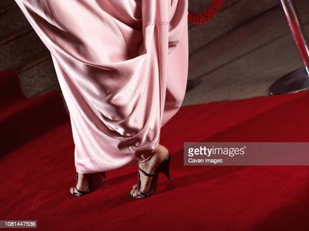 low section of woman wearing cocktail dress and high heels while walking on red carpet at event - red carpet event stock pictures, royalty-free photos & images