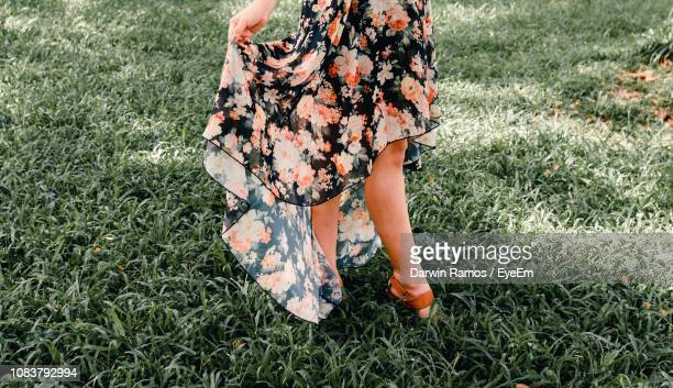 low section of woman wearing dress while standing on grassy field - robe à motif floral photos et images de collection