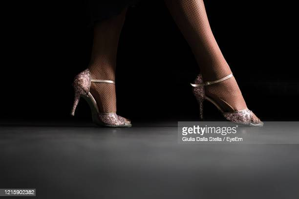 low section of woman wearing heels standing on floor against black background - open toe stock pictures, royalty-free photos & images