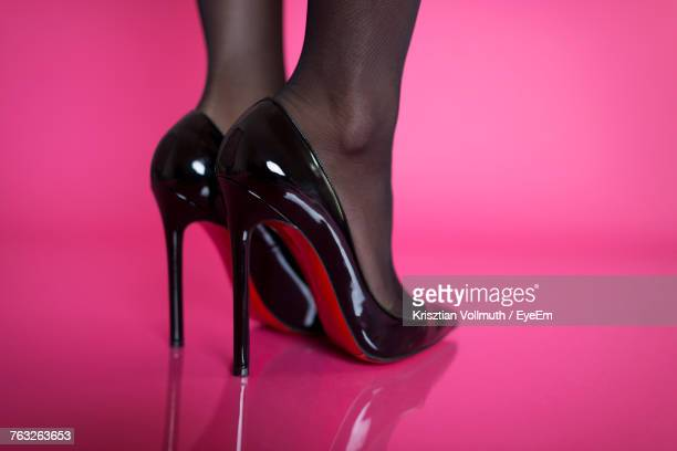 low section of woman wearing high heels against pink background - sapato preto - fotografias e filmes do acervo
