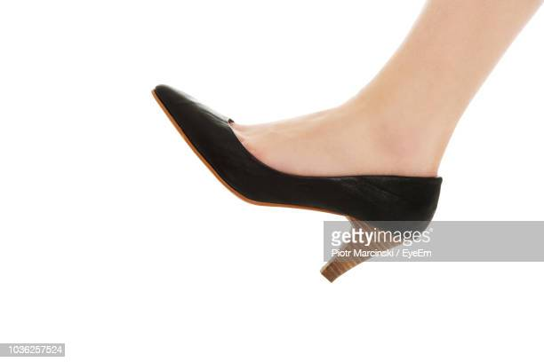 low section of woman wearing high heels against white background - ハイヒール ストックフォトと画像