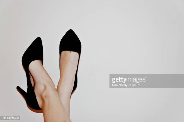 low section of woman wearing high heels against white background - high heels stock pictures, royalty-free photos & images