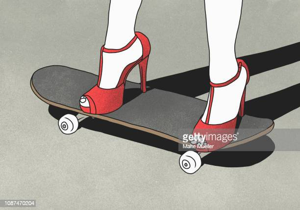 low section of woman wearing high heels and standing on skateboard - weiblichkeit stock-fotos und bilder