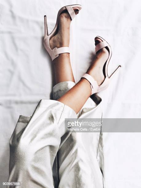low section of woman wearing high heels on bed - talons hauts photos et images de collection