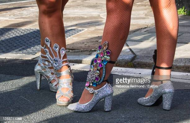 low section of woman wearing high heels on road - silver shoe stock pictures, royalty-free photos & images