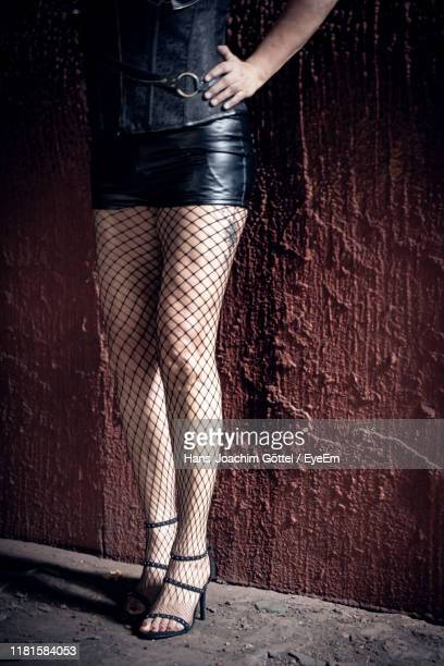 low section of woman wearing high heels while standing against wall - mini skirt stockings stock pictures, royalty-free photos & images