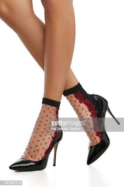 low section of woman wearing high heels while standing against white background - legs crossed at ankle stock pictures, royalty-free photos & images