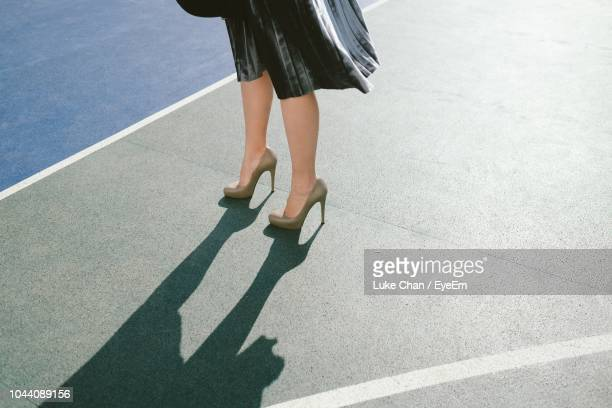 low section of woman wearing high heels while standing on street - hoge hakken stockfoto's en -beelden