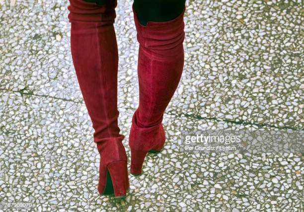 Low Section Of Woman Wearing High Heels While Walking On Footpath