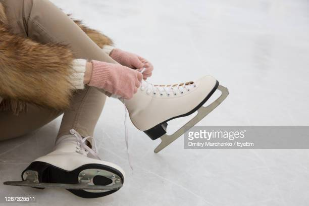 low section of woman wearing ice skate on snowy land - lace glove stock pictures, royalty-free photos & images