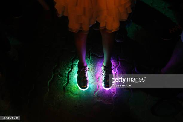 low section of woman wearing illuminated shoes standing on footpath at night - partie inférieure photos et images de collection