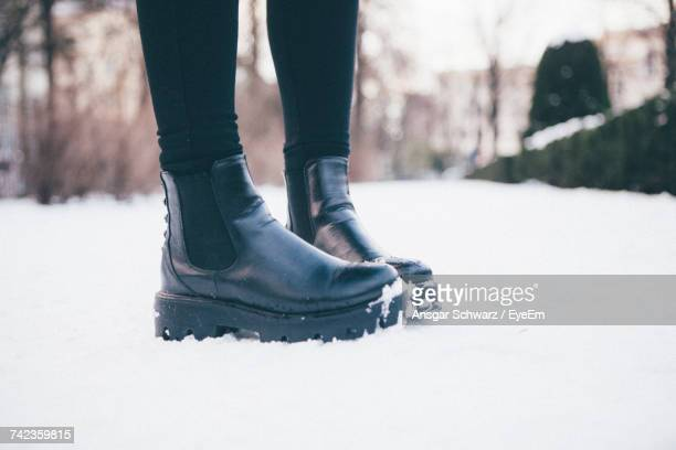 low section of woman wearing leather boots while standing on snowy field - ブーツ ストックフォトと画像