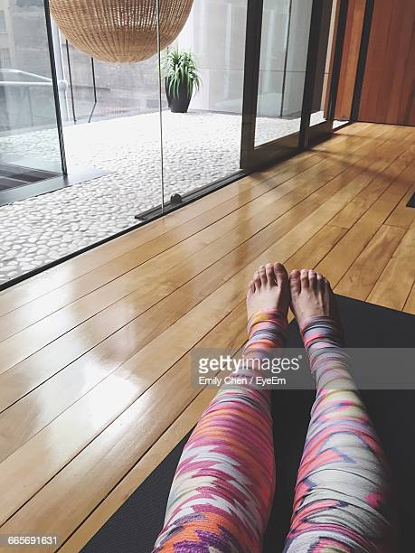 Low Section Of Woman Wearing Leggings While Sitting On Exercise Mat At Home