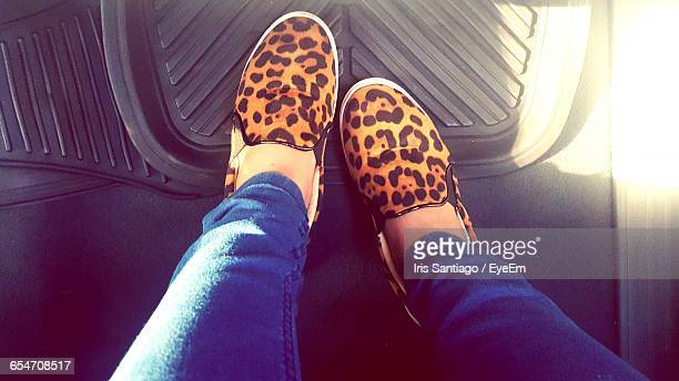 low section of woman wearing leopard print shoe in car - low section stock pictures, royalty-free photos & images
