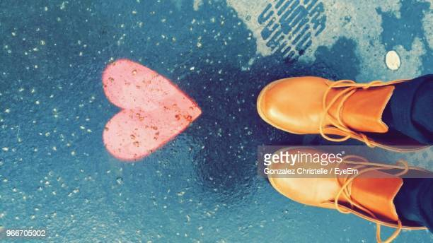 low section of woman wearing orange shoes by heart shape on wet street - orange shoe stock photos and pictures