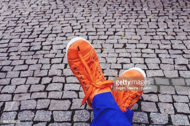 low section of woman wearing orange shoes on cobbled footpath - orange shoe stock photos and pictures