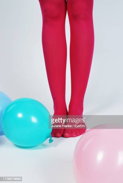 low section of woman wearing pink stockings standing with balloons against white background - nylon feet stockfoto's en -beelden