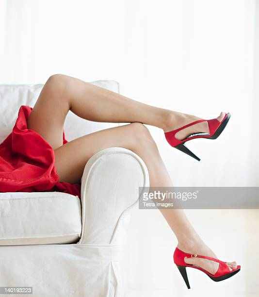 Low section of woman wearing red dress and shoes, studio shot