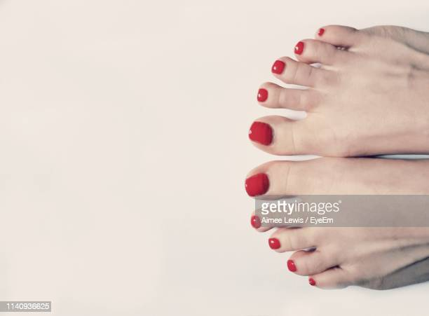 low section of woman wearing red nail polish standing over white background - toe stock pictures, royalty-free photos & images