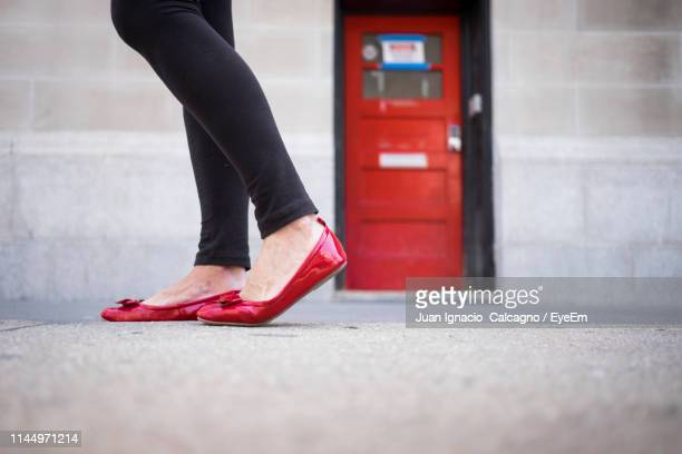 low section of woman wearing red shoes while walking on street - 人の足 ストックフォトと画像