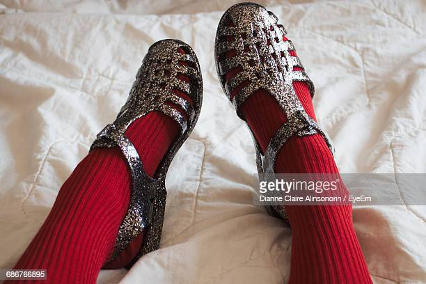 Low Section Of Woman Wearing Red Socks And Sandals On Bed