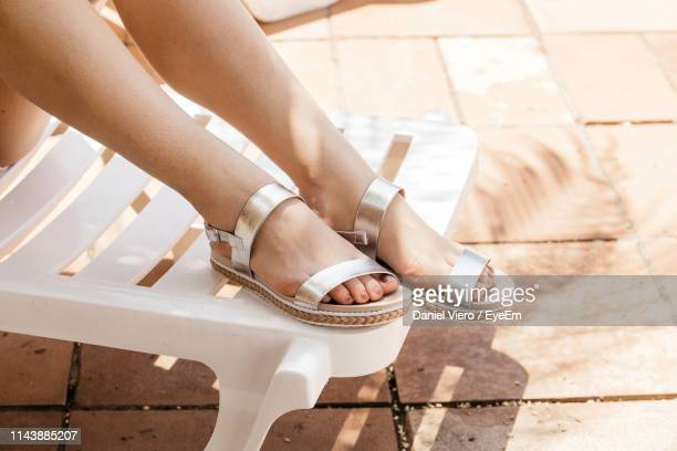 low section of woman wearing sandal while sitting on chair outdoors - open toe stock pictures, royalty-free photos & images
