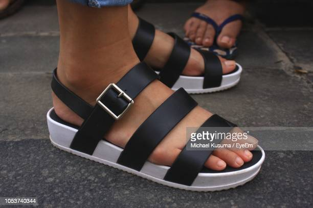 low section of woman wearing sandals standing on footpath - sandal stock pictures, royalty-free photos & images