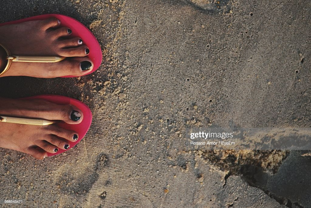 Low Section Of Woman Wearing Sandals Standing On Wet Sand At Beach : Stock Photo