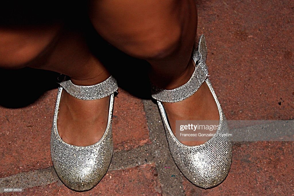 Low Section Of Woman Wearing Shiny Shoes On Footpath At Night : Stock Photo