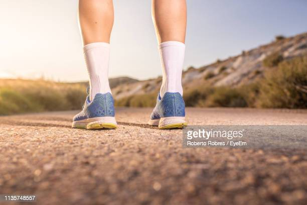 low section of woman wearing shoes and socks while standing on road - sock stock pictures, royalty-free photos & images