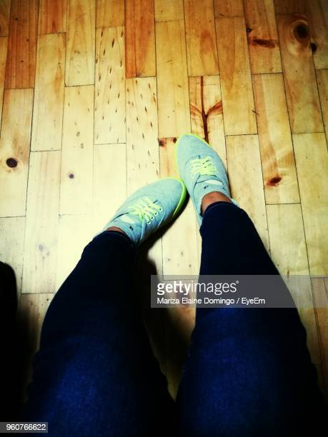 Low Section Of Woman Wearing Shoes On Floorboard