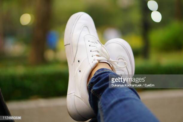 low section of woman wearing shoes outdoors - legs crossed at ankle stock pictures, royalty-free photos & images