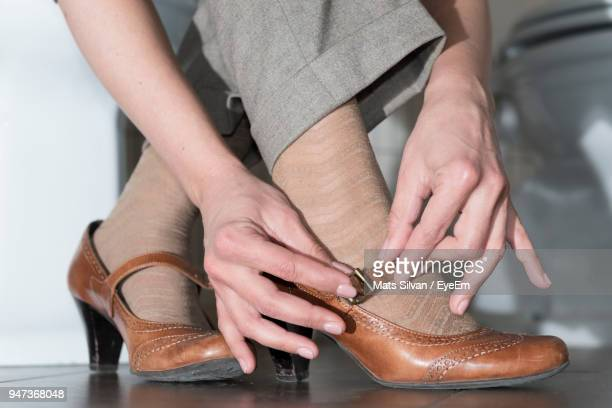 low section of woman wearing shoes - brown shoe stock photos and pictures
