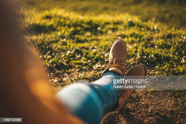 low section of woman wearing shoes relaxing on field - lace fastener stock pictures, royalty-free photos & images
