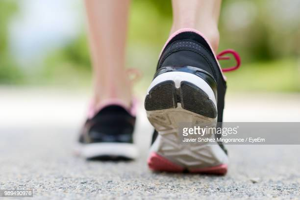 low section of woman wearing shoes walking on road - sports shoe stock pictures, royalty-free photos & images