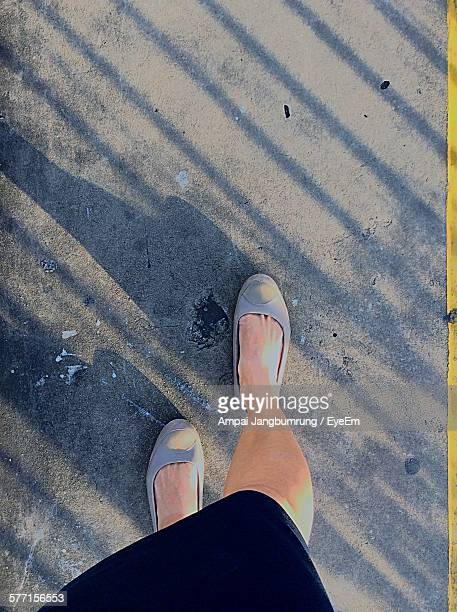 Low Section Of Woman Wearing Shoes Walking On Street