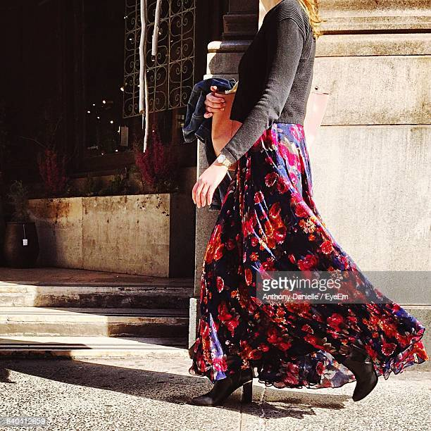 low section of woman wearing skirt walking on sidewalk - floral pattern skirt stock pictures, royalty-free photos & images