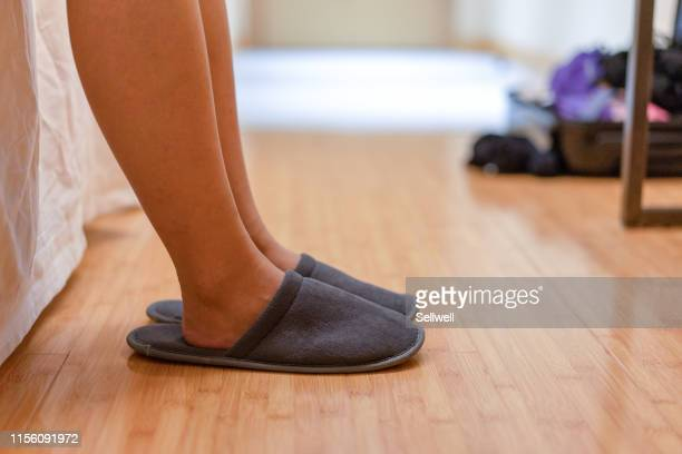 low section of woman wearing slippers on hardwood floor at bedroom - スリッパ ストックフォトと画像