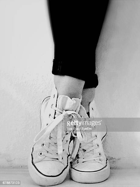 Low Section Of Woman Wearing Sneakers While Tiptoeing Against Wall