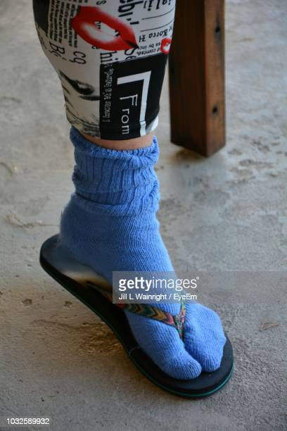 low section of woman wearing sock and flip-flop - ciabatta infradito foto e immagini stock