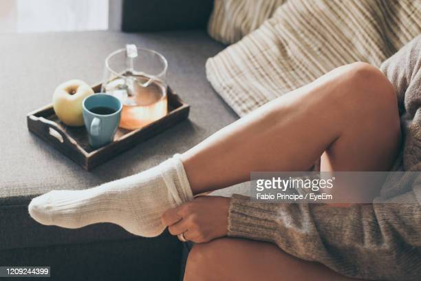 low section of woman wearing sock at home - sock stock pictures, royalty-free photos & images